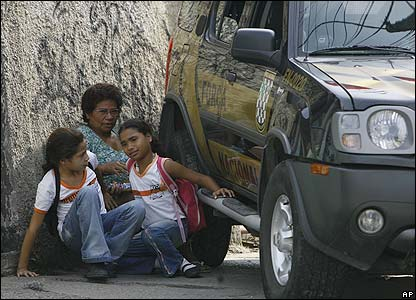 A young family hide behind a car