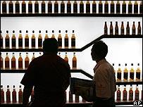 Men studying whisky bottles at an exhibition in Bangkok