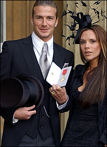David Beckham (left) shows off his OBE with wife Victoria
