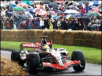 Lewis Hamilton drives his McLaren at the Goodwood Festival of Speed, watched by fans holding umbrellas