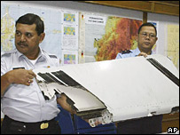 Two officials hold up the section of the missing plane