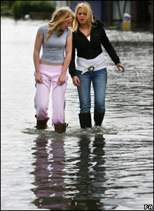 Two teenage girls wading through flood water in a street