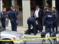 The professor lies on the ground surrounded by police