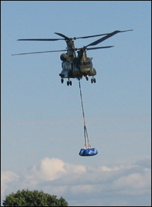 A Chinook helicopter transporting large sand bags