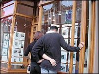 Couple looking at houses in estate agent's window