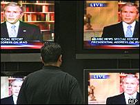 Un hombre mira por TV el anuncio de Bush