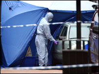 A police forensics officer examines a car