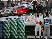 Lewis Hamilton helps marshals move his car after it stopped on the track in Magny-Cours