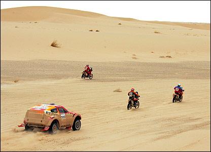 The Mitsubishi of last year's winner Luc Alphand passes some motorbikes during the sixth stage of the Dakar Rally between Tan Tan in Morocco and Zouerat in Mauritania on 11 January