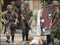 Mexican soldiers stand guard over a detained man in an operation in Apatzingan in May
