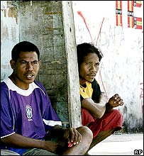 East Timorese men beside election graffiti