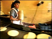 Lady carrying tortillas in shop