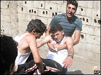 Protesters carry an injured man in northern Lebanon