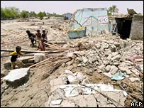 children pull bamboo sticks from collapsed houses in Turbat