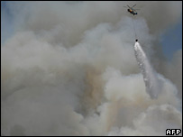A helicopter drops water on a fire in the Saittas area, central Cyprus