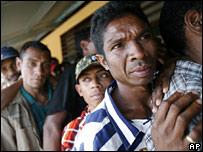 East Timorese men wait in line in Fatuahi Saturday, June 30, 2007