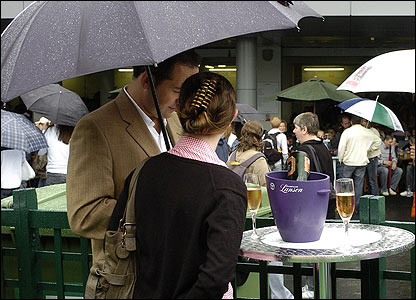 Tennis fans drink champagne under an umbrella