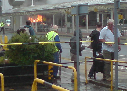 Travellers and commuters observing the burning vehicle