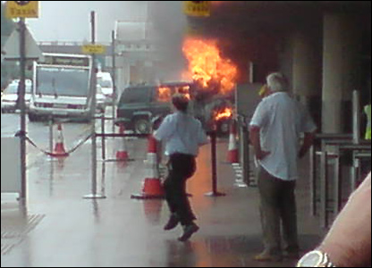 An image of billowing flames from the burning car, its nose against the terminal building