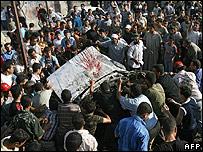 Palestinians gather around a car hit by an Israeli air strike, Gaza