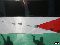 Palestinian gunmen shadowed by a huge Palestinian flag in Gaza