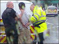 Dos policías arrestan a uno de los hombres. Foto: Michael McRanor