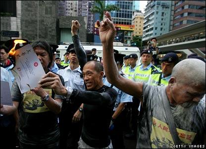 Man burns ceremony invitation on Hong Kong street, 1 July 2007