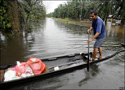 A villager shuttles food and provisions at a flooded village in Johor state