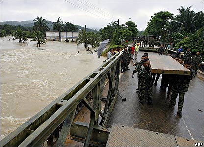 Army personnel build a temporary bridge over the Sembrong River in Johor state