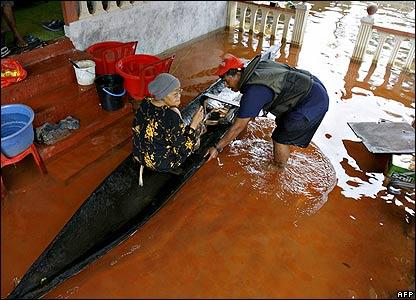 A flood relief volunteer prepares to evacuate senior village resident in Johor