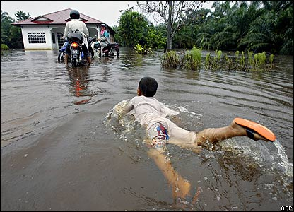 A child swims while residents ride their motorbikes out of rising flood waters