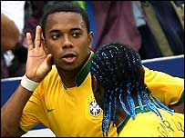 Robinho celebrates with team-mate Vagner Love after scoring against Chile