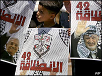 A Palestinian boy with Fatah supporters holding posters of Yasser Arafat and President Mahmoud Abbas