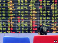 A Thai investor looks at stock prices on an electronic board at a private stock trading floor in Bangkok