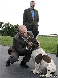 Former President George Bush Snr watches as President Vladimir Putin pats his dog