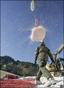 A helicopter transports snow in Kitzbuehel, Austria