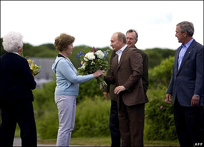 Vladimir Putin gives flowers to Laura Bush