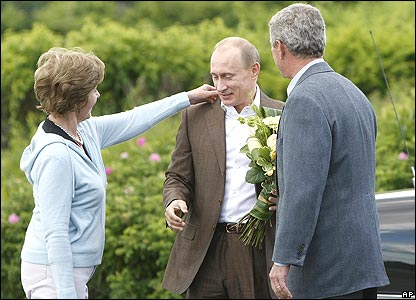 Laura Bush adjusts Vladimir Putin's collar, watched by George W Bush