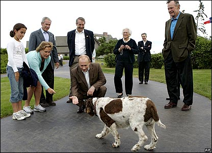 Vladimir Putin crouches to greet dog surrounded by Bush family