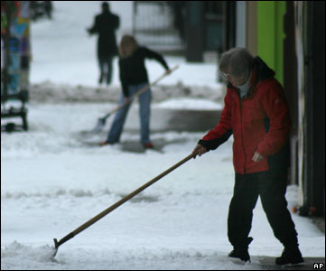 Sue Lunger, Columbia, Mo., attempts to scrape layers of ice from the sidewalk in front of her store
