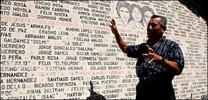 Pablo Alvarenga señala una pared poblada con los nombres residentes de Ciquera que murieron durante la guerra civil en El Salvador.