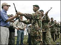 Peace commissioner Luis Carlos Restrepo (left) receives a rifle from disbanding paramilitaries (File photo, 2005)