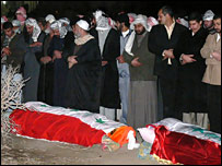 Iraqis look at the coffins of the two men