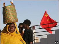A Sudanese woman walks past a Chinese flag in Khartoum