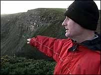 David Sneap points to the cliff