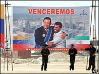 Members of the Revolutionary Guard stand under a banner of Iranian President Mahmoud Ahmadinejad and Venezuelan President Hugo Chavez.
