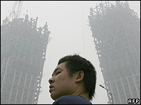 A Chinese man walks near the China Central Television headquarters, which is lost in the haze in central Beijing, 03 July 2007.
