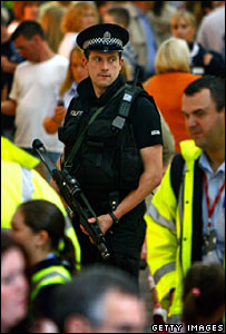 An armed police officer stands in the crowds at Glasgow Airport