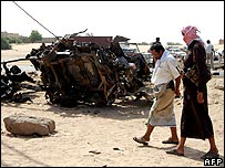 People walk past bomb damaged car