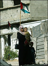 Woman and children walk through ally in Khan Younis in southern Gaza
